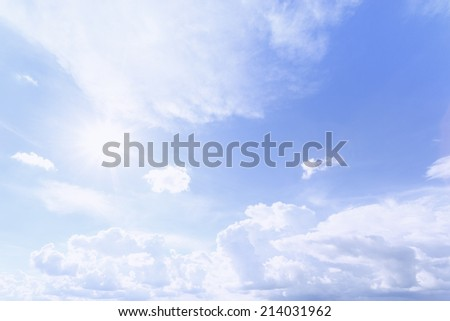 Bright blue sky with clouds and sun