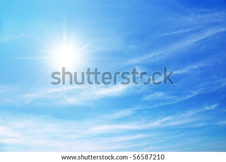bright blue sky with sun shining and some clouds - stock photo