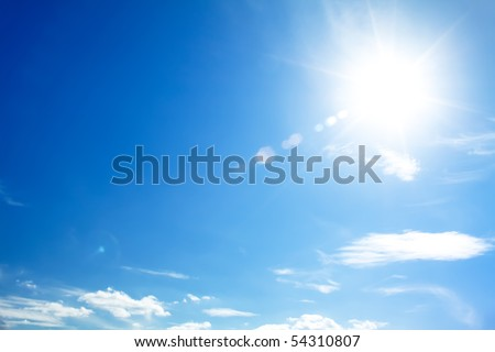 bright blue sky with the sun causing lens flare - stock photo