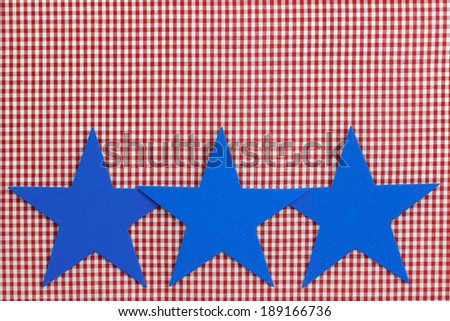 Bright blue stars on red checkered (gingham) background - stock photo