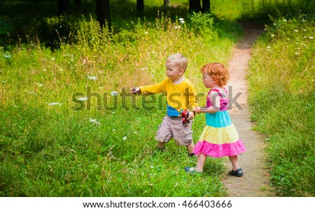 bright boy and girl. children holding hands whlie walking through the park. Portrait of happy kids on a bright sunny day. Friendship. Summer holidays.