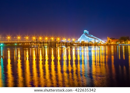 Bright bridge and night reflections in Daugava river. Modern National Library of Latvia in Riga