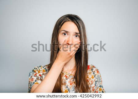 bright brunette girl frightened and closes the mouth with his hands, isolated on a gray background - stock photo