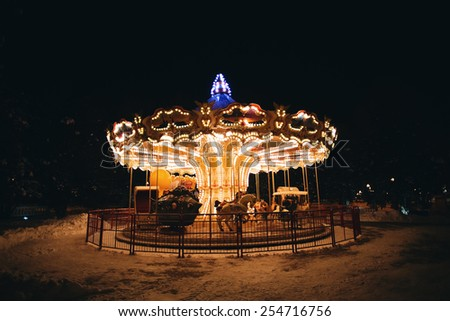 bright carousel at dark night in cold winter - stock photo