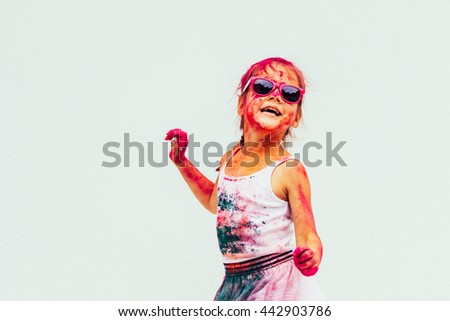 Bright cheerful and happy little girl with Indian colors in glasses