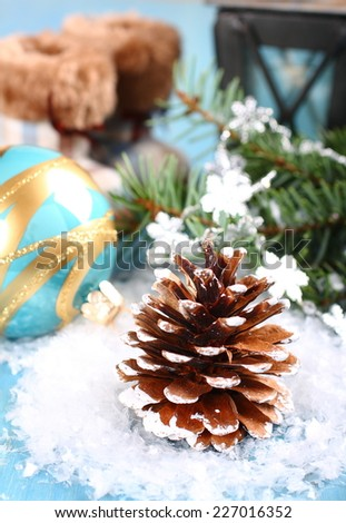 Bright  christmas composition with pinecone,  blue ball and boots on snow