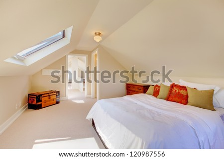 Bright clean attic bedroom in the small home with beige carpet. - stock photo