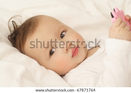 bright closeup portrait of adorable baby with toy - stock photo