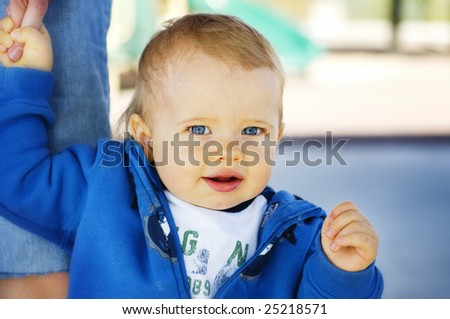 Bright closeup portrait of adorable happy baby with blue eyes