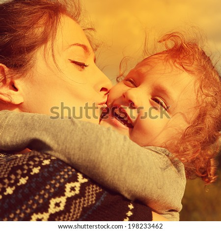 Bright closeup portrait of happy mother kissing laughing daughter. Instagram effect. Happiness of family love. - stock photo