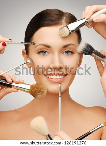 bright closeup portrait picture of beautiful woman with brushes - stock photo