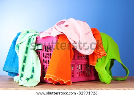 Bright clothes in a laundry basket on blue background - stock photo