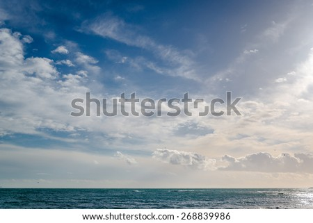 Bright cloudy sky and horizon over the sea - stock photo