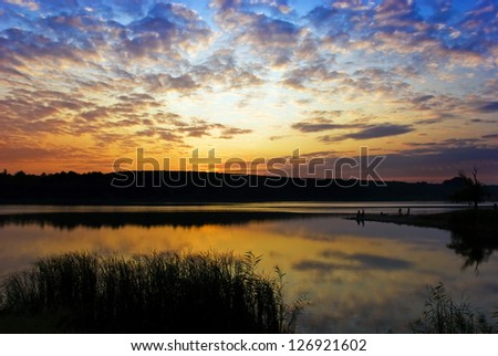 bright cloudy sunset above the lake - stock photo