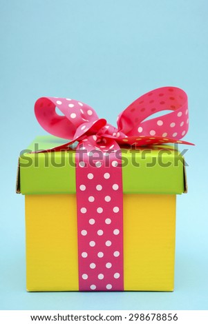 Bright color yellow and green gift box with pink polka dot ribbon on pink and blue background.  - stock photo