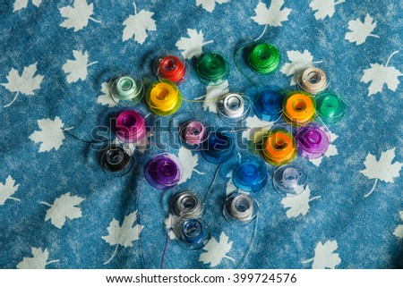 bright colored thread and bobbin on a blue denim background - stock photo