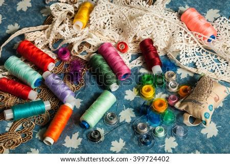 bright colored thread, bobbin, tape lace on blue denim background - stock photo