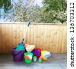 Bright colorful buckets for cleaning, on a background of a spring garden - stock photo