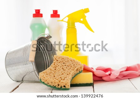 Bright colorful cleaning set on a white wooden table - stock photo