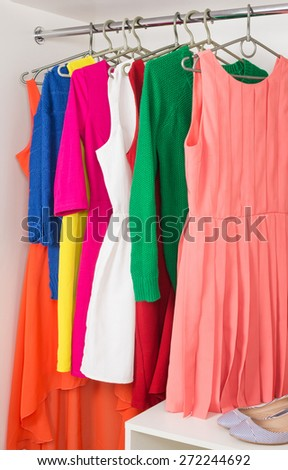 bright colorful female dresses and sweaters  hanging on coat hanger,  shoes and handbag in white wardrobe