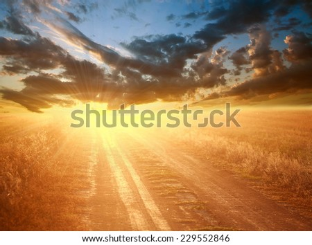 Bright colorful sunset over country road on the background of a dramatic sky