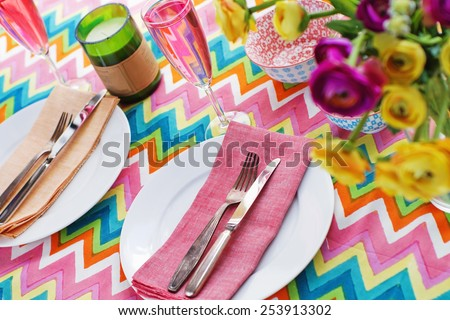 Bright colorful table setting with multi-colored chevron pattern tablecloth - stock photo