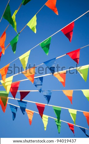 Bright colorful triangle flag banner above blue sky background - stock photo