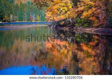 Bright colors of autumn reflected by clear lake - stock photo