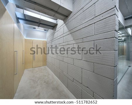 Bright corridor with the glowing lamps in the office in a loft style. There is a gray brick wall and wooden walls with several wooden doors. Horizontal..
