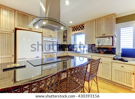 Bright cozy kitchen room with beige cabinets and white ceiling - stock photo