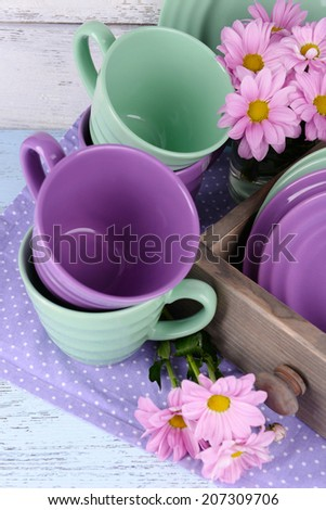 Bright dishes with flowers in crate on wooden background