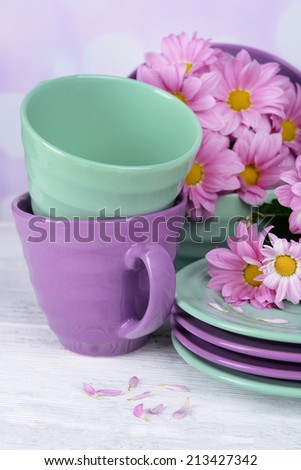 Bright dishes with flowers on table on bright background - stock photo