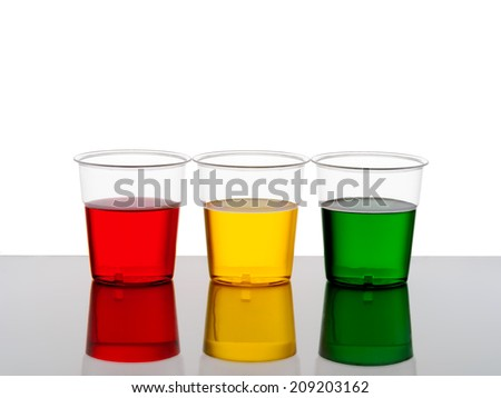 Bright drinks in traffic light colours, plastic cups. Drink drive warning maybe or just beautiful! Red yellow / orange green alcohol or cordial. - stock photo