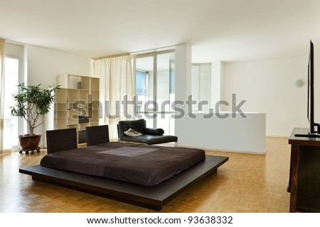 Bright duplex with hardwood floors, large room with double bed - stock photo