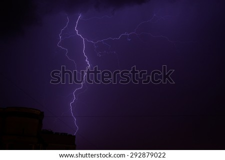 Bright electric blue lightning strike at night with dark storm sky - stock photo
