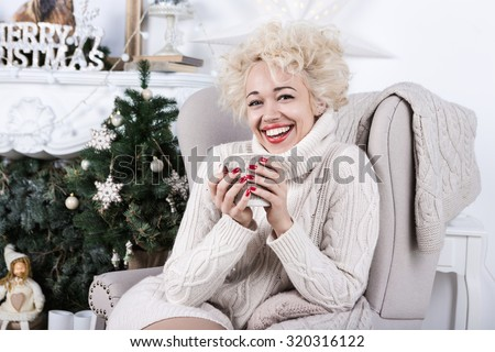 Bright emotions of the New Year holiday. Merry Christmas. Beautiful smiling woman sitting in a comfortable chair beige. The stylish interior decoration. Series of winter holiday photos. - stock photo