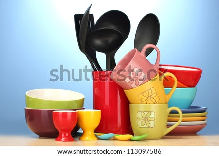 bright empty bowls, cups and kitchen utensils on wooden table on blue background - stock photo