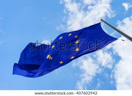 Bright EU flag against the blue sky closeup. EU symbol - stock photo