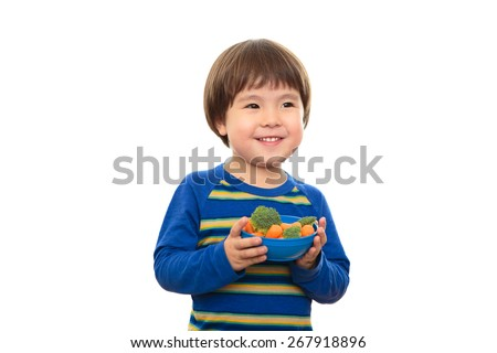 Bright eyed three year old boy holding blue bowl filled with broccoli and carrots, isolated on a white background. Little child eating healthy food and vegetables for a snack. Happy and healthy living