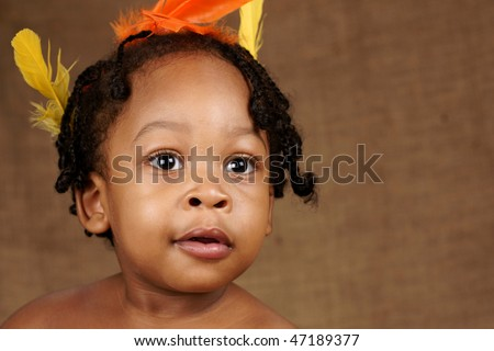 bright eyed toddler with feathers in hair - stock photo