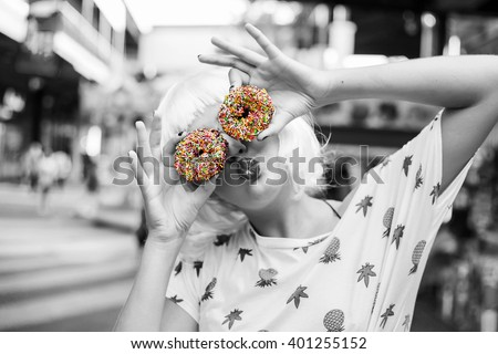 bright fashion funny girl in pink wig posing on background carousel at an amusement park. The hands holding the sweet donuts. Black-and-white photography with a color separation of a donut. - stock photo