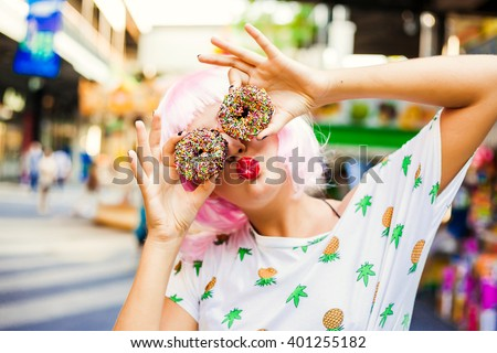 bright fashion funny girl in pink wig posing on background carousel at an amusement park. The hands holding the sweet donuts. - stock photo