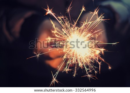 bright festive Christmas sparkler in hand toning - stock photo