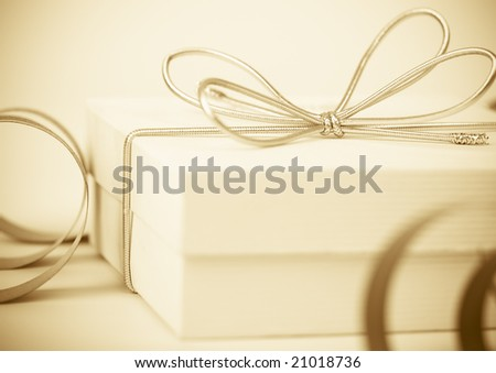 Bright festive colored background with gift in box and twirled ribbon - stock photo