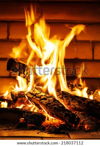 Bright Fire from Firewood in Fireplace, on a brick wall background - stock photo