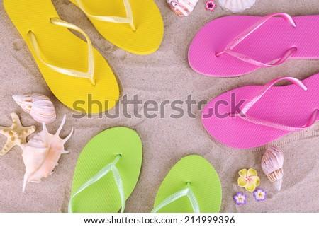 Bright flip-flops on sand, close up - stock photo