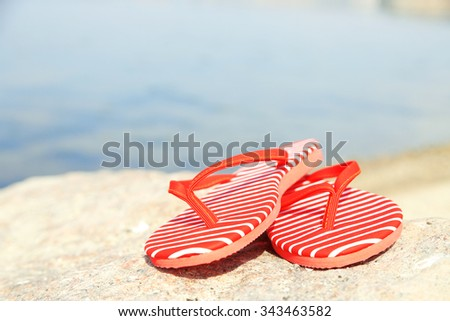 Bright flip-flops on stone, nature background