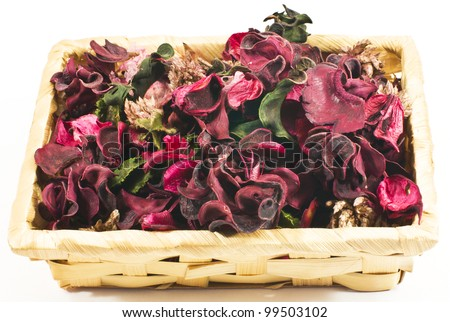 bright flower petals in a wicker basket close up on white background