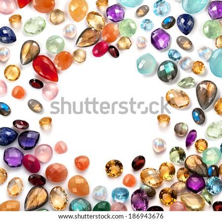 Bright gemstones on white background. Mix of real stones such as: amethyst, moonstone, sapphire, blue topaz, aventurine, peridot, rose quartz, labradorite, citrine, carnellian, garnet, lapis lazuli .. - stock photo
