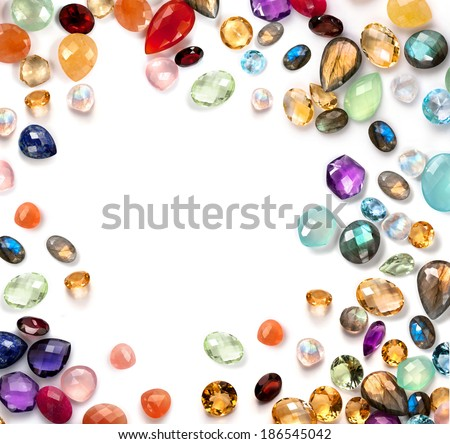 Bright gemstones on white background. Real polished stones: amethyst, sapphire, blue topaz, peach and rainbow moonstone, labradorite, garnet, ruby, chalcedony, lapis lazuli, aventurine, peridot ... - stock photo